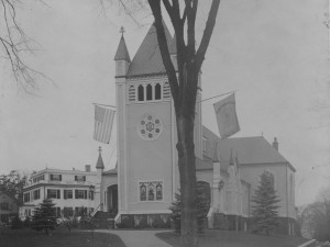 """Church and Rectory, circa 1918 - flags commemorating the end of World War I and welcoming home the troops hang from the tower """"For God and Country - Welcome Home"""""""